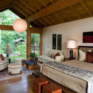 Example of a large zen master dark wood floor and brown floor bedroom design in New York with white walls