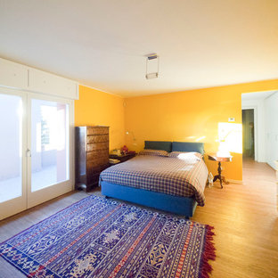Inspiration for a large eclectic master bamboo floor bedroom remodel in Milan with yellow walls
