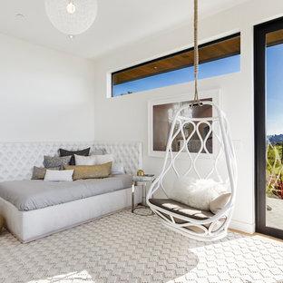 Imagen de dormitorio actual con paredes blancas, suelo de madera clara y marco de chimenea de ladrillo