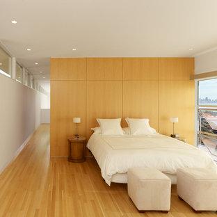 Foto på ett funkis sovrum, med vita väggar, mellanmörkt trägolv och gult golv
