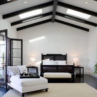 Exempel på ett medelhavsstil huvudsovrum, med vita väggar, mörkt trägolv och svart golv
