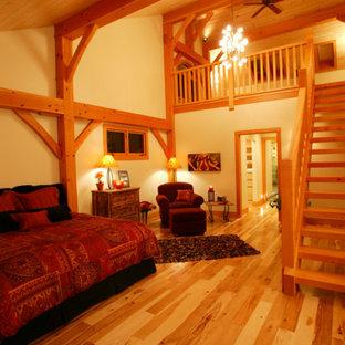 Diseño de dormitorio tipo loft, de estilo de casa de campo, grande, con paredes beige y suelo de madera clara