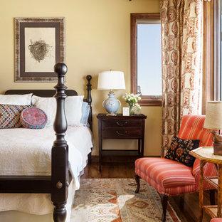 デンバーの中サイズのサンタフェスタイルのおしゃれな寝室 (黄色い壁、濃色無垢フローリング、茶色い床) のレイアウト