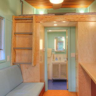 Immagine di una piccola camera da letto stile loft minimalista con pareti blu, pavimento in sughero e nessun camino