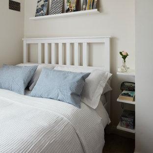 Modelo de dormitorio actual, pequeño, con paredes blancas, moqueta, chimenea de esquina, marco de chimenea de metal y suelo beige
