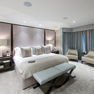 Mid-sized contemporary master bedroom in London with beige walls, carpet, no fireplace, black floor, coffered and wallpaper.