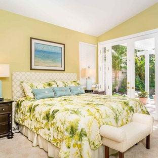 This is an example of a small beach style guest bedroom in Los Angeles with green walls, carpet, no fireplace and beige floor.
