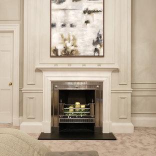На фото: большая хозяйская спальня в классическом стиле с серыми стенами, ковровым покрытием, стандартным камином, фасадом камина из штукатурки и серым полом с