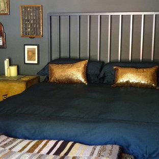 Diseño de dormitorio principal, ecléctico, de tamaño medio, con paredes grises, suelo de madera en tonos medios, estufa de leña, marco de chimenea de piedra y suelo marrón