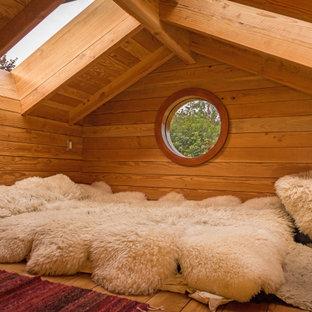 Idée de décoration pour une petit chambre mansardée ou avec mezzanine craftsman avec un mur marron, un sol en bois brun et un sol marron.