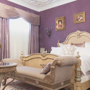 Imagen de dormitorio clásico con paredes púrpuras, suelo de madera oscura, chimenea tradicional y marco de chimenea de yeso