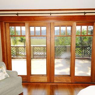 サンディエゴの中サイズのトロピカルスタイルのおしゃれな主寝室 (ベージュの壁、淡色無垢フローリング、標準型暖炉、木材の暖炉まわり、茶色い床) のレイアウト
