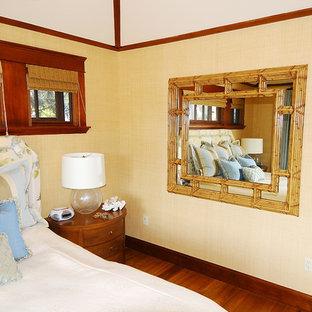 Diseño de dormitorio principal, exótico, de tamaño medio, con paredes beige, suelo de madera clara, chimenea tradicional, marco de chimenea de madera y suelo marrón