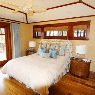 サンディエゴの中サイズのトロピカルスタイルのおしゃれな主寝室 (ベージュの壁、淡色無垢フローリング、茶色い床、標準型暖炉、木材の暖炉まわり) のレイアウト