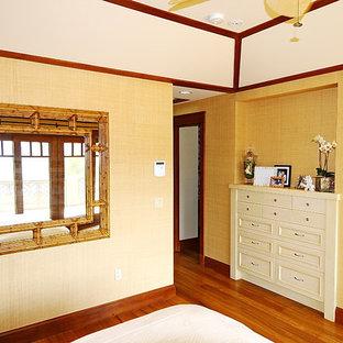 Modelo de dormitorio principal, tropical, de tamaño medio, con paredes beige, suelo de madera clara, chimenea tradicional, marco de chimenea de madera y suelo marrón