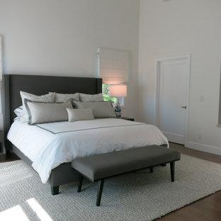 Imagen de dormitorio principal y abovedado, contemporáneo, grande, con paredes blancas, suelo de madera en tonos medios, chimenea de doble cara y suelo marrón