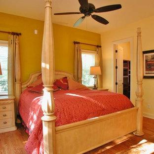 アトランタの広いヴィクトリアン調のおしゃれな主寝室 (黄色い壁、無垢フローリング) のインテリア