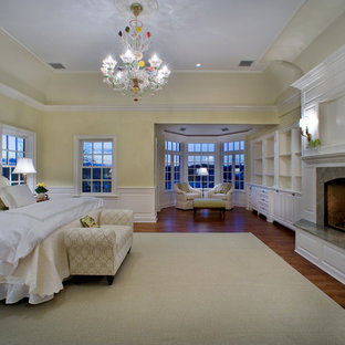 Photo of a large traditional master bedroom in New York with yellow walls, medium hardwood floors, a standard fireplace, a stone fireplace surround and brown floor.