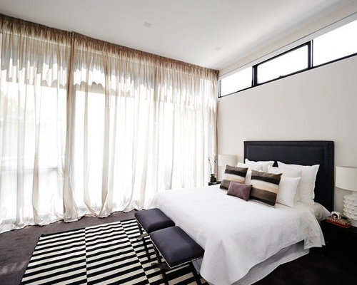 mid sized trendy bedroom photo in melbourne with white walls and carpet
