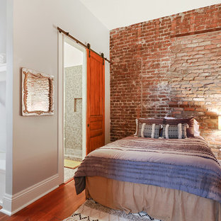 Bedroom - industrial medium tone wood floor and brown floor bedroom idea in New Orleans with gray walls