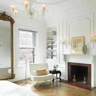 Klassisk inredning av ett sovrum, med vita väggar, mellanmörkt trägolv, en standard öppen spis och en spiselkrans i tegelsten