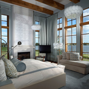 Photo of a large contemporary master bedroom in Orlando with blue walls, a standard fireplace, dark hardwood floors, a concrete fireplace surround and brown floor.