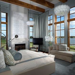Großes Modernes Hauptschlafzimmer mit blauer Wandfarbe, Kamin, dunklem Holzboden, Kaminumrandung aus Beton und braunem Boden in Orlando