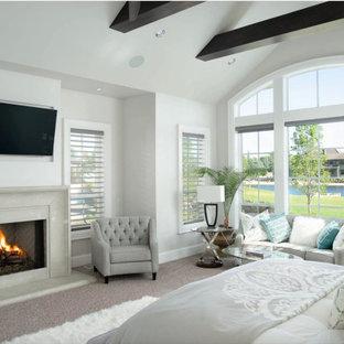 На фото: спальня в средиземноморском стиле с серыми стенами, ковровым покрытием, стандартным камином, серым полом, балками на потолке и сводчатым потолком с