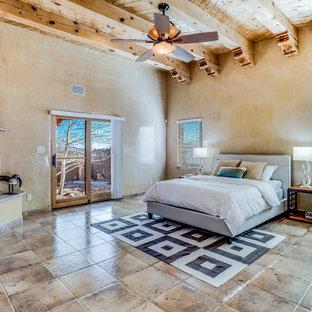 Свежая идея для дизайна: большая хозяйская спальня с желтыми стенами, полом из терракотовой плитки, угловым камином, фасадом камина из штукатурки и коричневым полом - отличное фото интерьера