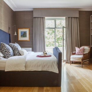 Photo of a classic bedroom in London with beige walls and light hardwood flooring.