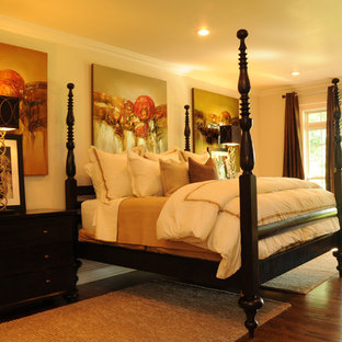 Ispirazione per una camera da letto tradizionale con pareti beige e pavimento in legno massello medio