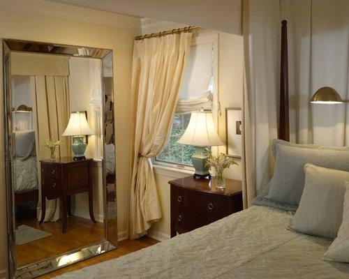 example of a classic medium tone wood floor bedroom design in newark with beige walls