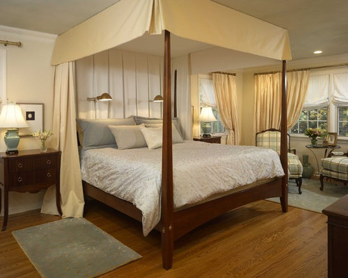 Traditional medium tone wood floor bedroom idea in Newark with beige walls