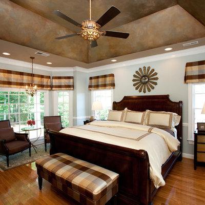 Elegant medium tone wood floor bedroom photo in Charlotte with gray walls