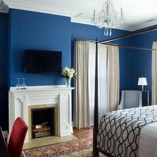Diseño de habitación de invitados tradicional, grande, con paredes azules, chimenea tradicional, marco de chimenea de baldosas y/o azulejos, suelo de madera en tonos medios y suelo marrón