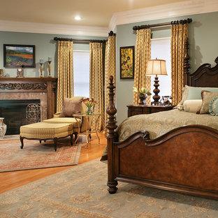 Modelo de dormitorio principal, clásico, con paredes grises, suelo de madera en tonos medios, chimenea tradicional y marco de chimenea de piedra