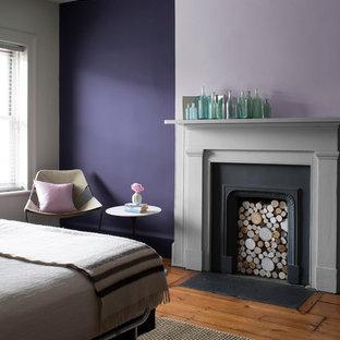 Свежая идея для дизайна: спальня с фиолетовыми стенами, паркетным полом среднего тона, стандартным камином и фасадом камина из штукатурки - отличное фото интерьера