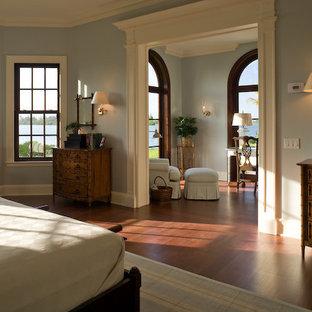 Mid-sized elegant master medium tone wood floor bedroom photo in Miami with gray walls