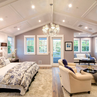 Elegant medium tone wood floor bedroom photo in Los Angeles with gray walls and a standard fireplace