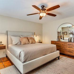 Ejemplo de dormitorio principal, de estilo americano, grande, sin chimenea, con paredes beige, suelo de baldosas de terracota y suelo naranja