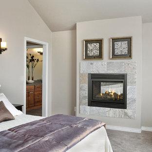 Imagen de dormitorio principal, clásico, de tamaño medio, con paredes beige, moqueta, chimeneas suspendidas, marco de chimenea de baldosas y/o azulejos y suelo gris