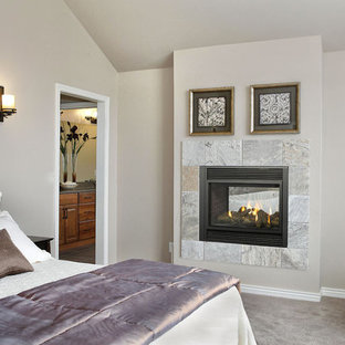 Bedroom - mid-sized traditional master carpeted bedroom idea in New York with beige walls, a two-sided fireplace and a stone fireplace