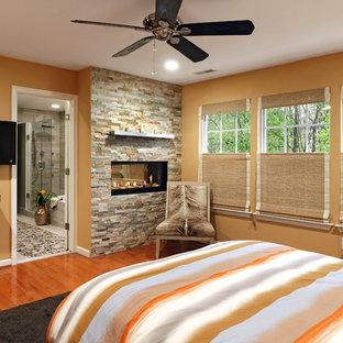 На фото: хозяйская спальня среднего размера в стиле современная классика с оранжевыми стенами, паркетным полом среднего тона, фасадом камина из камня, двусторонним камином и оранжевым полом с