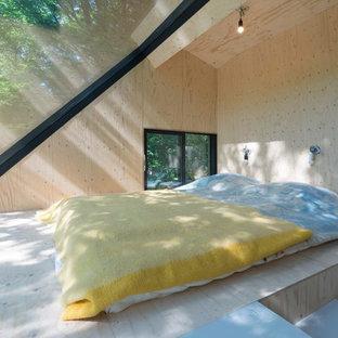 Immagine di una piccola camera matrimoniale minimal con pavimento in compensato