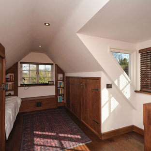Small country loft-style bedroom in Kent with white walls, dark hardwood floors and no fireplace.