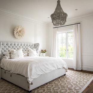 他の地域の広いトランジショナルスタイルのおしゃれな主寝室 (白い壁、無垢フローリング、茶色い床、パネル壁) のインテリア