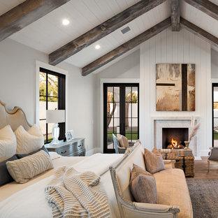 Idéer för att renovera ett lantligt sovrum, med grå väggar, mellanmörkt trägolv, en standard öppen spis, en spiselkrans i sten och brunt golv
