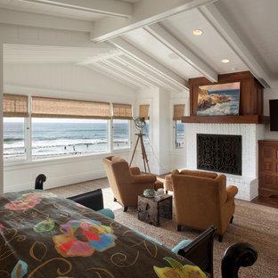 Ejemplo de dormitorio costero con paredes blancas, chimenea tradicional y marco de chimenea de ladrillo