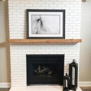 Ejemplo de habitación de invitados grande con paredes grises, suelo laminado, chimenea tradicional, marco de chimenea de ladrillo y suelo gris
