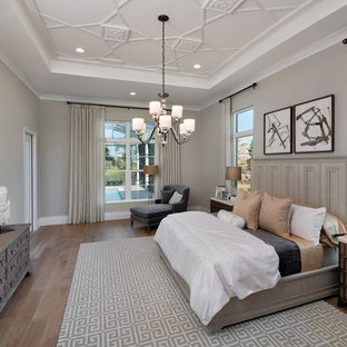 Example of a transitional master medium tone wood floor and brown floor bedroom design in Miami with beige walls
